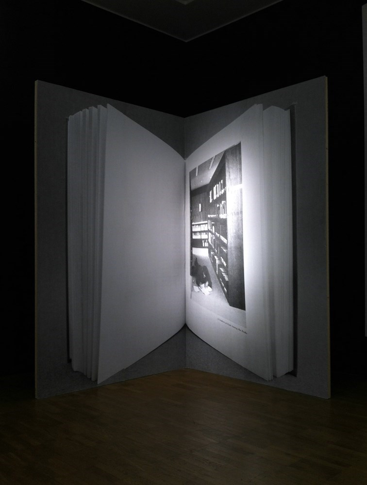 A student at ease among the books, 260 cm x 328 cm, b&w prints on wood, 2013<br />installation view Kumu Art Museum Tallin